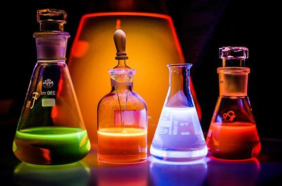 chemist adding green liquid to test tubes with two other chemists ...