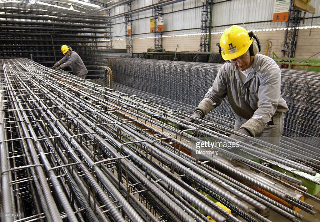 Workers build columns of rebar to be used in construction at ...