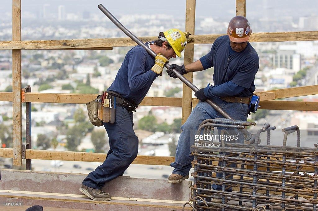 Iron Workers Bending Rebar On Construction Site Stock Photo ...