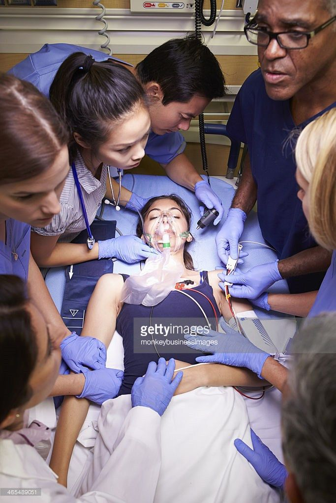 Six Medical Staff In Blue Treating Patient In Emergency Room Stock ...