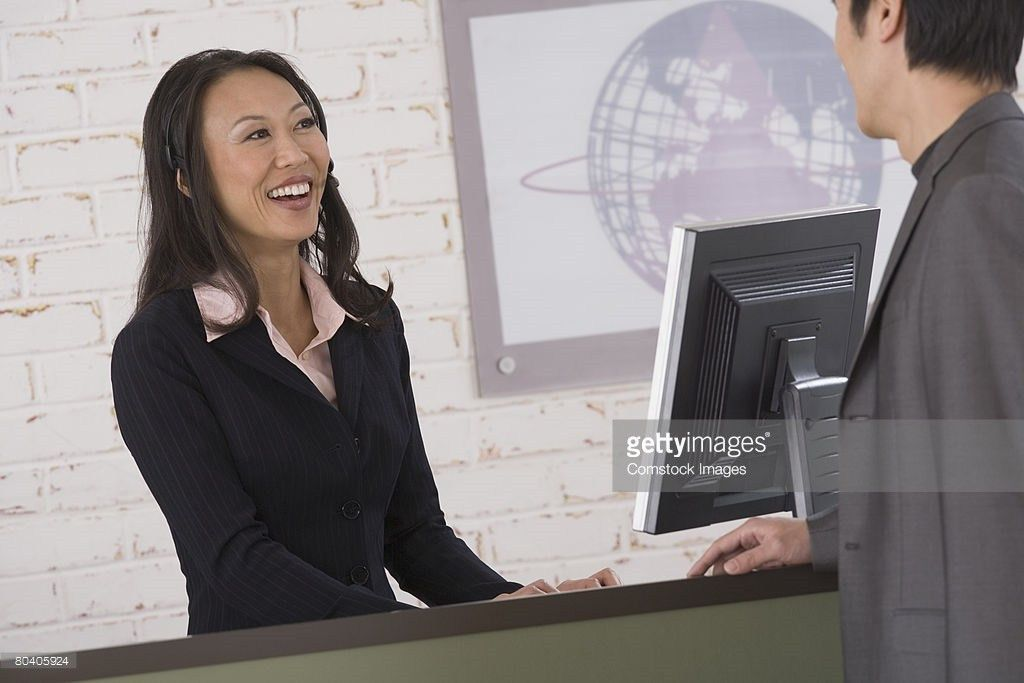 Receptionist Smiling At Businessman From Behind Front Desk Stock ...