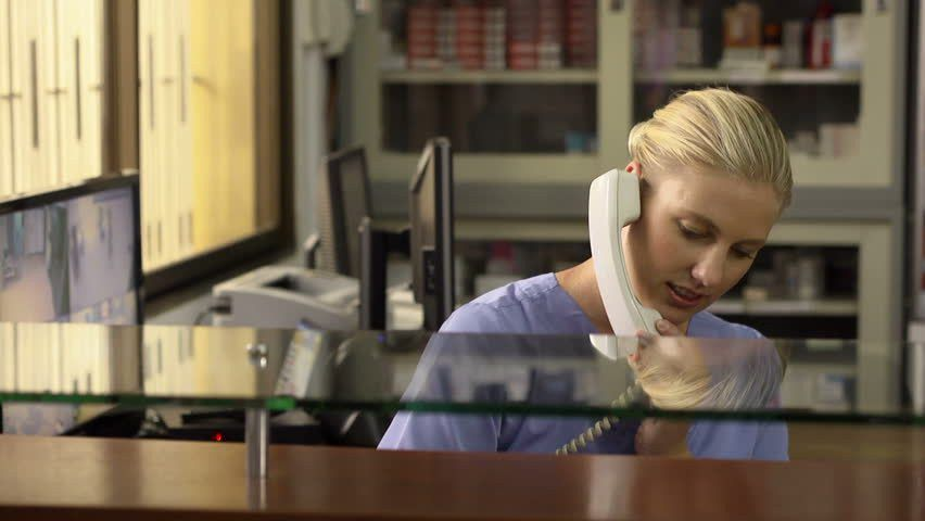 Young Woman At Work As Receptionist And Nurse In Hospital And ...