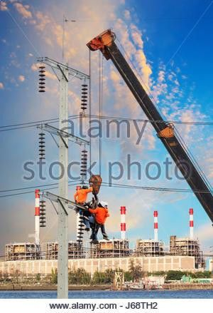 electrician worker working on high voltage electric pole with ...