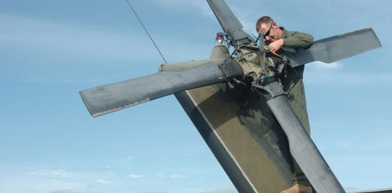 Aviation mechanic working on rotor blades. The UH-60 helicopter ...