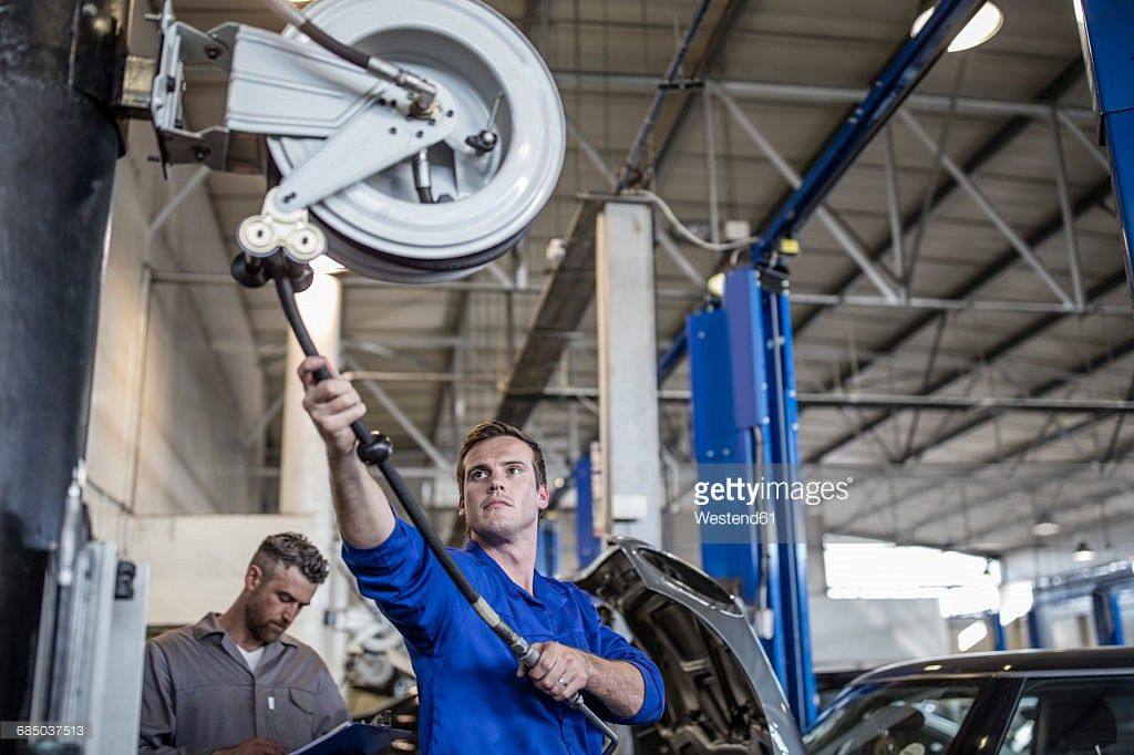 Car Mechanic In A Workshop Pulling On Hose Machine Stock Photo ...