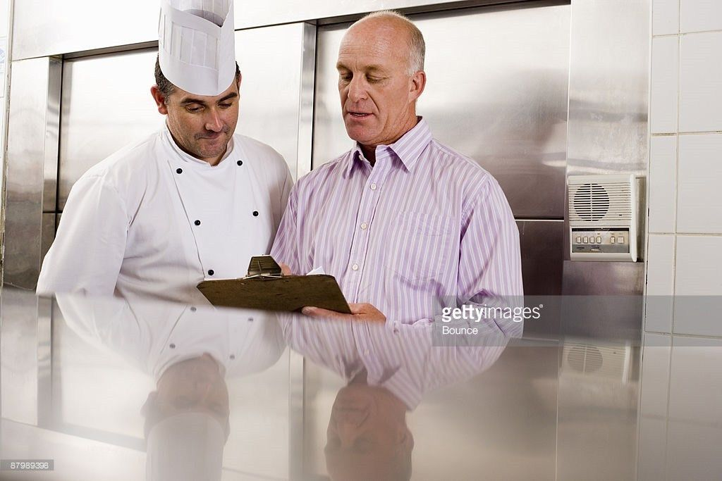 Male Chef And Restaurant Manager Talking In Commercial Kitchen ...