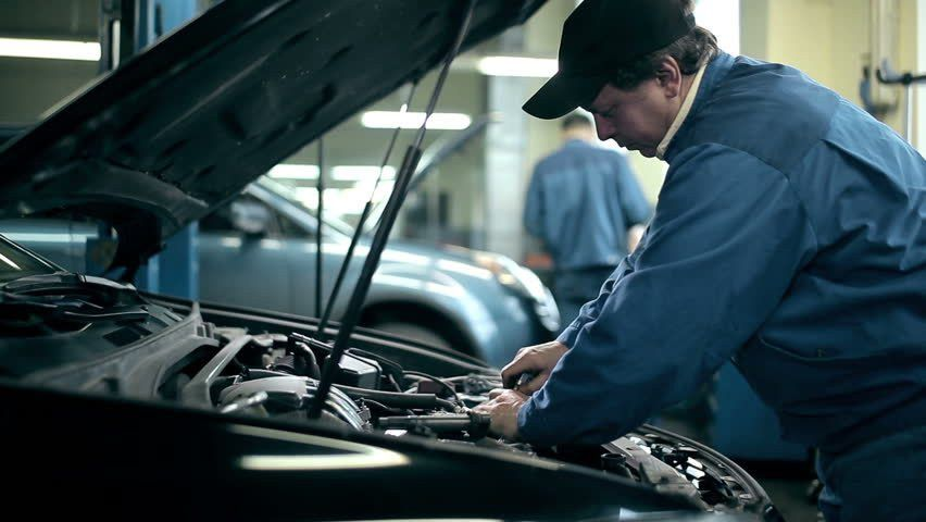 Car Service, Male Mechanic Checks Current Flow Automobile, Writes ...