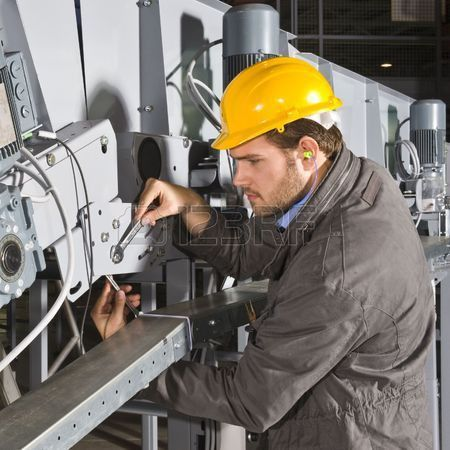 A Male Maintenance Engineer At Work On An Industrial Appliance ...
