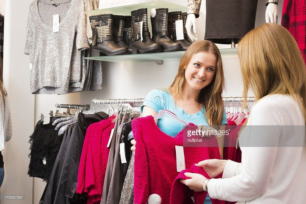 Salesperson Talking To Customers In Fashion Store Stock Photo ...