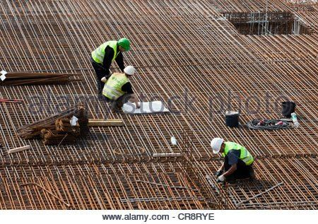 Construction worker installing steel rebar beams for reinforced ...