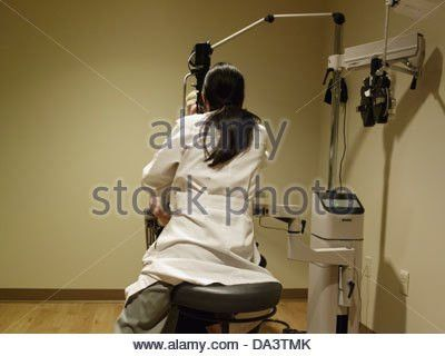 A Caucasian Ophthalmologist assistant examines the eyes of a 77 ...