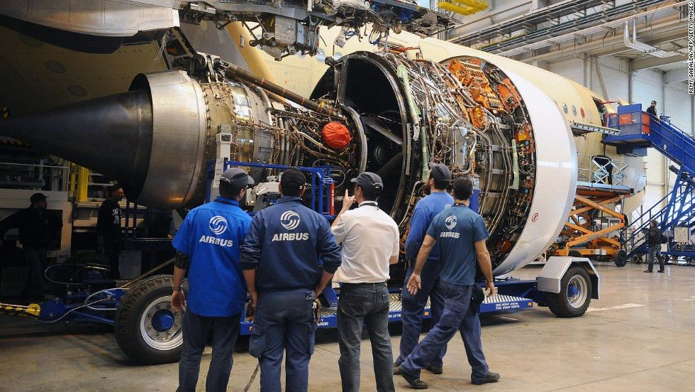 Technicians look at a Rolls-Royce jet engine, provided by UTC ...