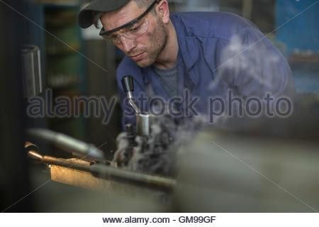 Mechanic wearing safety goggles using drilling machine in workshop ...