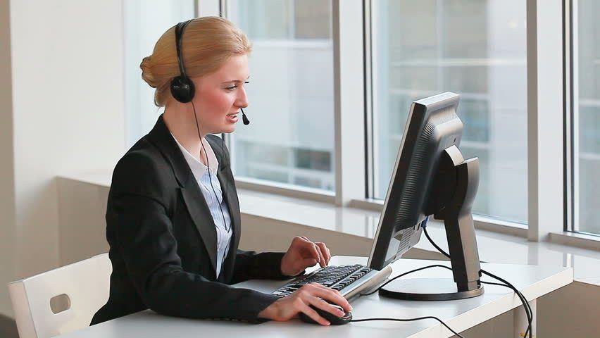 Attractive Help Desk Consultant Talking On Headset And Working On ...