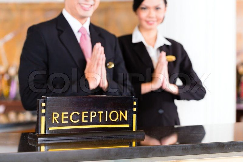 Chinese Asian reception team at luxury hotel front desk welcoming ...