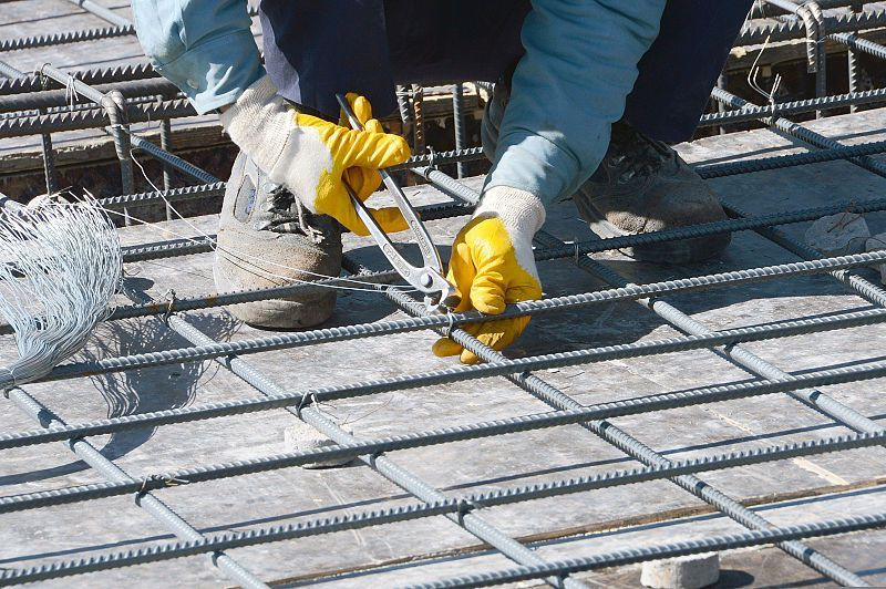 File:A worker ties together reinforcing bar, or rebar, to ...