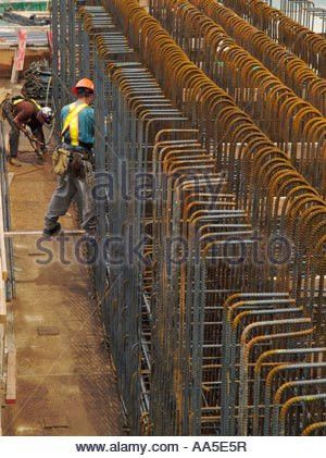Construction workers installing steel rebar beams for reinforced ...