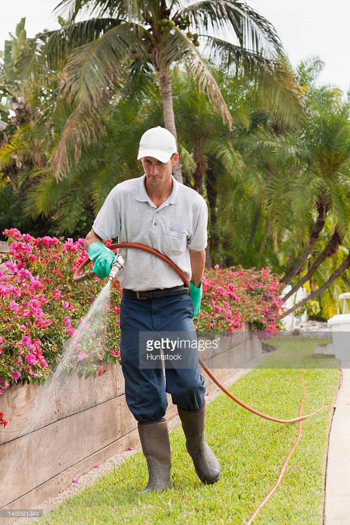 Pest Control Technician Using High Pressure Spray Gun And Hose On ...