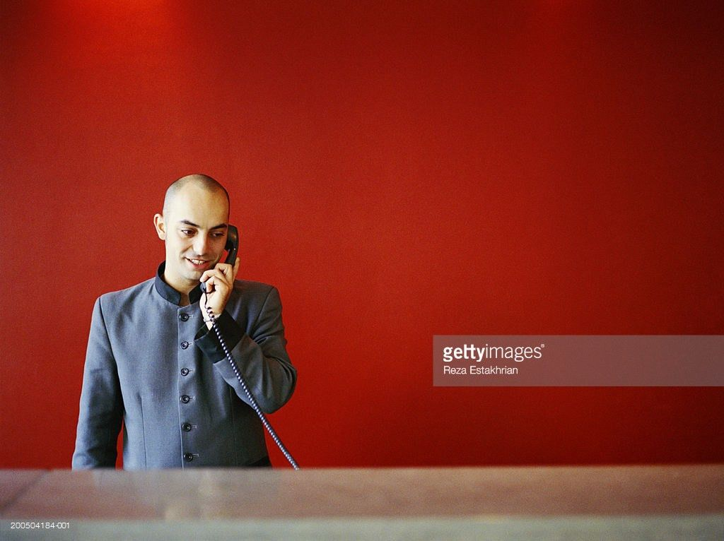 Hotel Front Desk Receptionist Answering Telephone Stock Photo ...