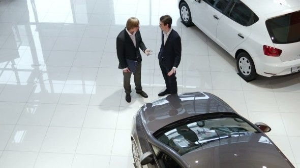 Sales Manager And Customer In Car Showroom by photo_oles | VideoHive