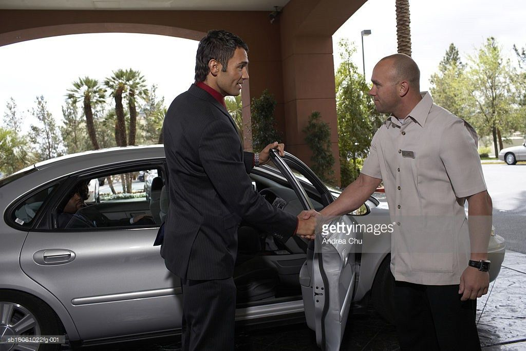 Hotel Porter Shaking Hands With Business Man Outside Car Side View ...