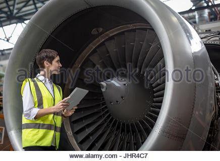 Female aircraft maintenance engineer examining turbine engine of ...