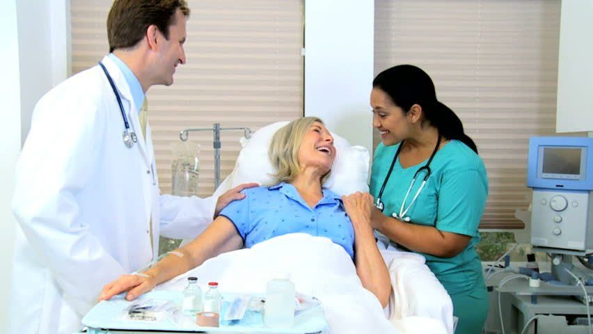 Diverse Medical Staff Provides Bedside Care And Reassurance To An ...