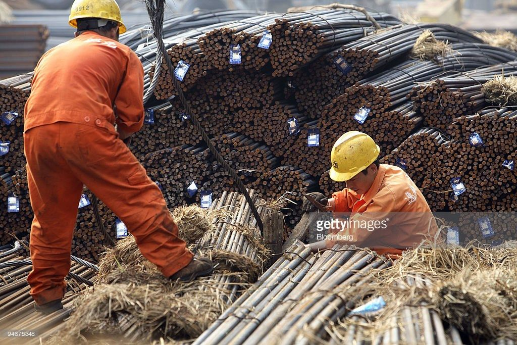Workers attempt to hoist up a load of steel rebar at a steel ...