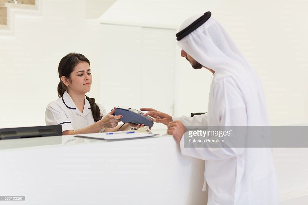 Arab Man Paying Bill To Receptionist In Hospital Stock Photo ...