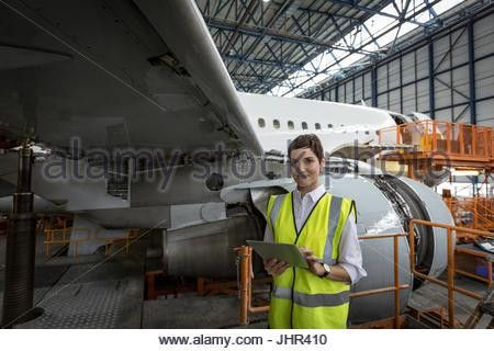 Portrait of female aircraft maintenance engineer standing with ...