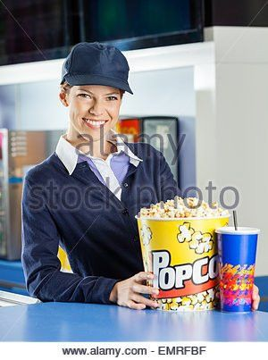 Confident Worker Holding Popcorn At Cinema Concession Stand Stock ...