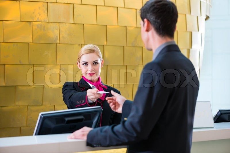 Man in Hotel check in at reception or front office being given key ...
