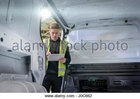 Apprentice vehicle inspector inspecting interior of vehicle in car ...
