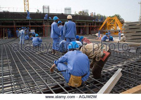 Workers working on rebar reinforced concrete frame on a building ...