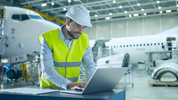 Engineer is Working on Computer in Aircraft Maintenance Hangar by ...