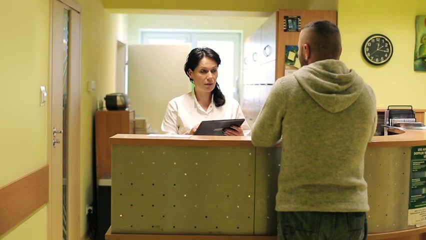 Patient And Nurse With Tablet Conversing At Hospital Reception ...