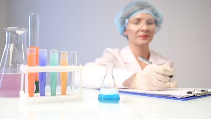 Calm, Woman Chemist, Lab Technician With Safety Glasses Is Pouring ...