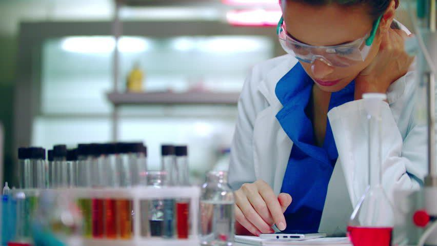 Young Female Chemist Working With Laptop And Chemicals In Lab ...