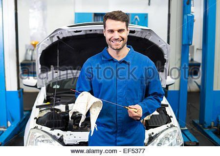 Young Happy Male Mechanic Testing Car Battery With Multimeter ...