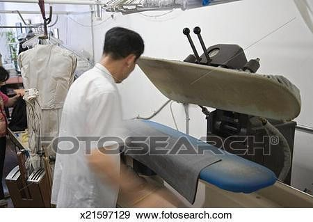 Stock Photograph of Man pressing trousers in laundry presser ...