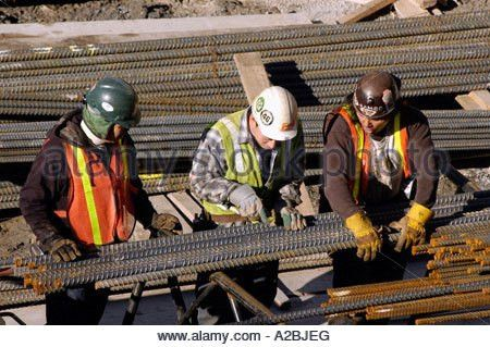 Construction workers building rebar supports for concrete wall ...