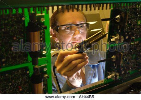 Production operator soldering circuit boards at Axiom ...