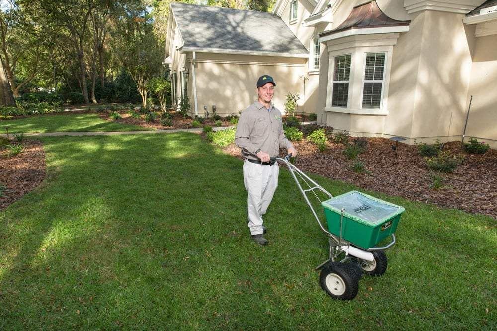 Joe, our lawn technician, fertilizing a lawn to promote healthy ...