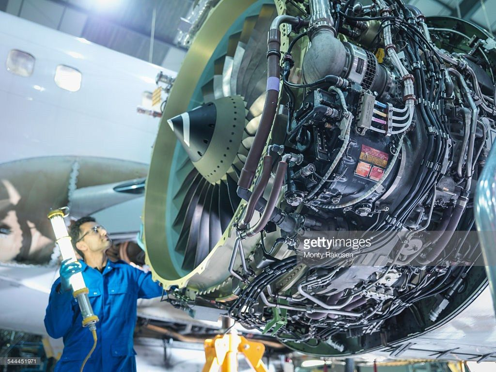 Engineers Working On Aircraft Wing In Aircraft Maintenance Factory ...