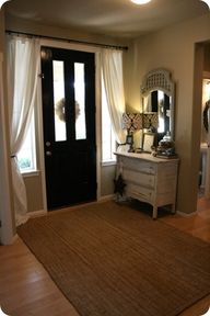 Curtain rod above the door and curtains tied back for the sidelights; can be closed for privacy at night.