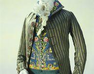 traje (chaqueta, chaleco y pantalón) 1790-Francia- Material:Escudo de seda azul y verde de tafetán a rayas y raso; fold-back cuello de pie, recortada de dobladillo, chaleco de seda faya con arco romano bordado, cuello de pajarita.  En este chaleco son arcos delicadamente bordados y filas de columnas en el estilo de la antigua Roma. Durante la segunda mitad del siglo 18, bajo la influencia del neoclasicismo, las antiguas ruinas romanas y góticas y los resto fueron adoptados por la pintura.