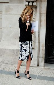 Black sweater, black and white tie dye printed knee length skirt with sandals and black leather Hermes Collier bracelet