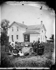 A family sits around a table on which is a wooden box with a key lock and a hinged lid, possibly with a mirror inside the lid. (a jewelry box? a music box?) The children have a doll and a doll bed. Behind them is a frame house with double doors off the inside corner of the open porch (c. 1872). #Victorian #vintage #portraits #family