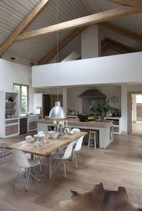 A huge open plan living space with plenty of options for communal seating such as a modern dining area and kitchen bar area. Hardwood flooring throughout brings a sense of cohesion to this contemporary interior.