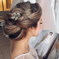 With a messy bun in the back and tendrils in the front and maybe on the side